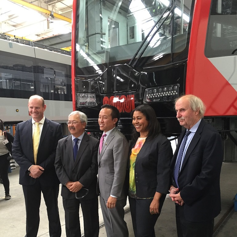 Four men and one woman in suits stand in front of a light rail vehicle on stands, waiting to have the wheel trucks installed.