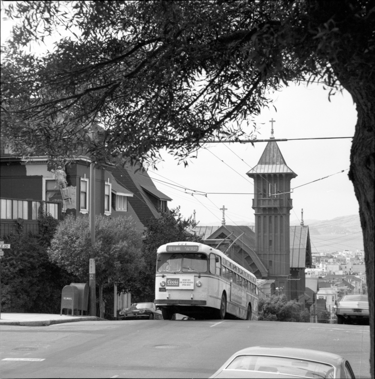 Looking north on Fillmore and Steiner showing trolley coach cresting steep hill in Pacific Heights.