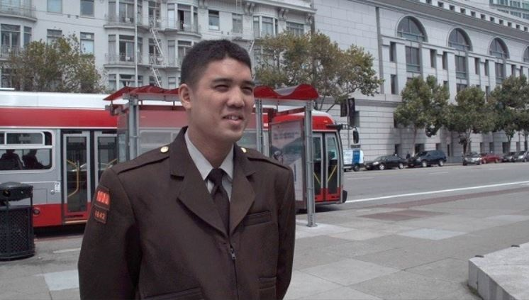 Man in a brown Muni uniform stands on a city street in front of a transit shelter and bus.