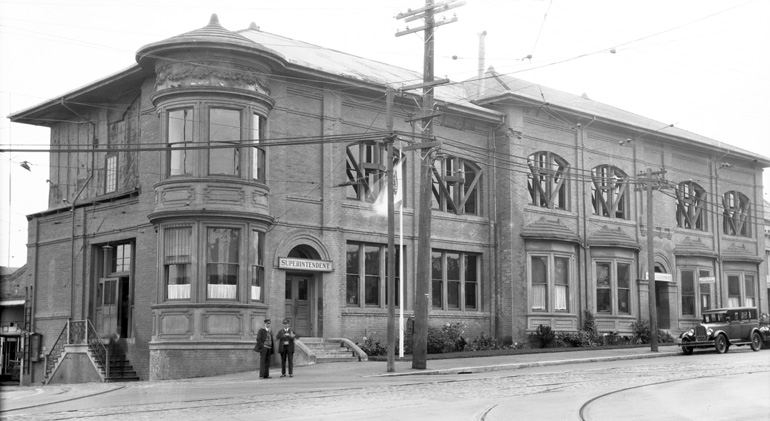 A two-story Victorian building with a round corner-turret presides over the intersection at Geneva and San Jose avenues, with two streetcar operators in dark uniforms standing outside on the street corner. The building is a Romanesque-style red brick complex known as the Geneva Car House, built in 1901 to serve as an office and car house for one of the first electric streetcar lines in a city that at the time was dominated by cable cars. A transit hub long before the existence of BART, the Balboa Park neighborhood already had a stop for the Southern Pacific train line. In fact, the present-day BART station is in almost the exact same spot as the long-gone train stop and the Southern Pacific line followed the route of today's I-280 freeway.