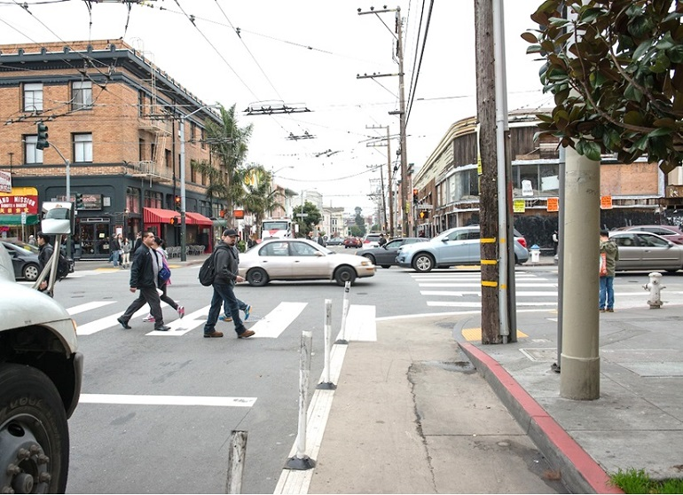 A view of busy Mission and 19th streets, with a painted safety zone on the sidewalk corner.