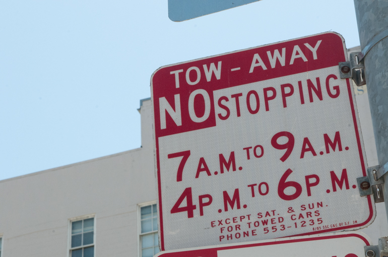 "Low-angle photo of red and white ""Tow Away, No Stopping"" street sign with a blue sky in the background."