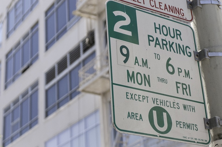 RPP white and green street sign announcing two-hour parking except vehicles with Area U permits.