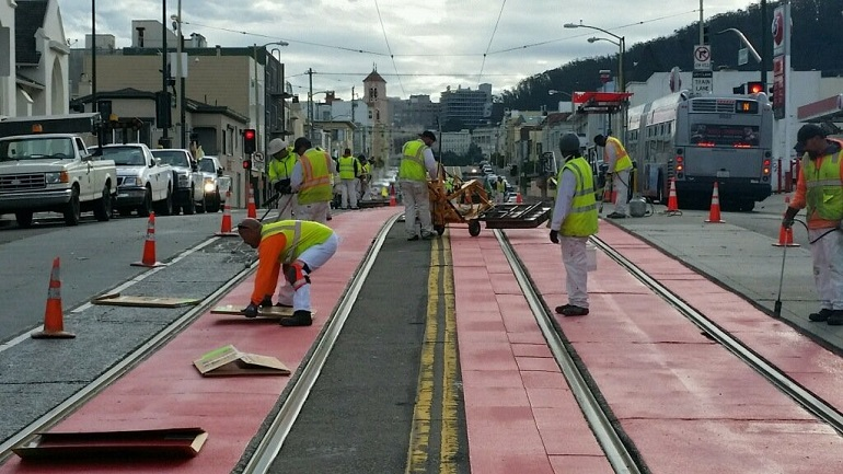 Paint crew of nine men in white pants and shirts with yellow safety vests works in the middle of Judah Street looking east to install the red thermoplastic tiles around the center trackway.