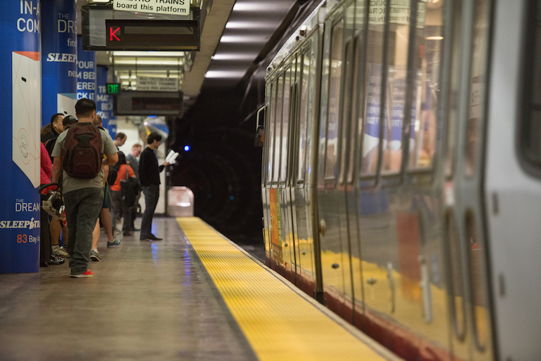 Muni customers stand behind the bright yellow strip on a subway platform as the light rail train pulls in on the right.