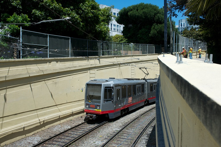 Gray N Judah light rail vehicle emerges from the Sunset Tunnel portal in Cole Valley.