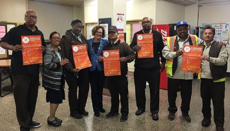 Men and women stand in a line holding orange posters to announce Transit Week.