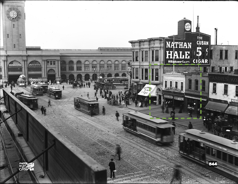 Black and white photograph taken August 22, 1905 showing lower Market Street between Steuart Street and present day Embarcadero (then called East Street). In view are the Ferry Building and cable cars. Across Market Street is a row of buildings and storefronts, below which lies a wooden plank sidewalk with people walking. One building in the image is highlighted by a box drawn in a green dotted line on the image to indicate the area detailed in the next image.