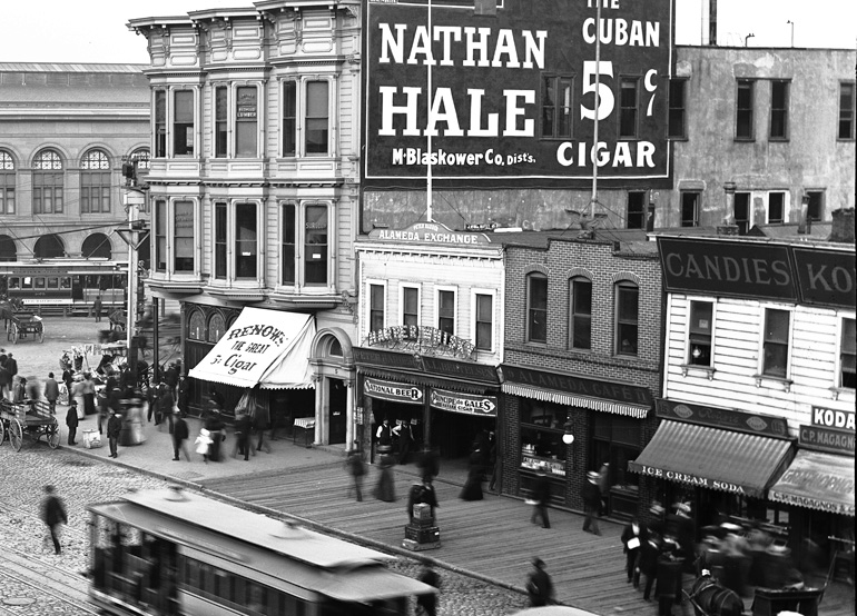 A zoomed-in view of an area highlighted in the previous photograph, showing a view of Market Street near today's Embarcadero, showing a busy wooden sidewalk and businesses with Victorian storefronts, including the Alameda Exchange.