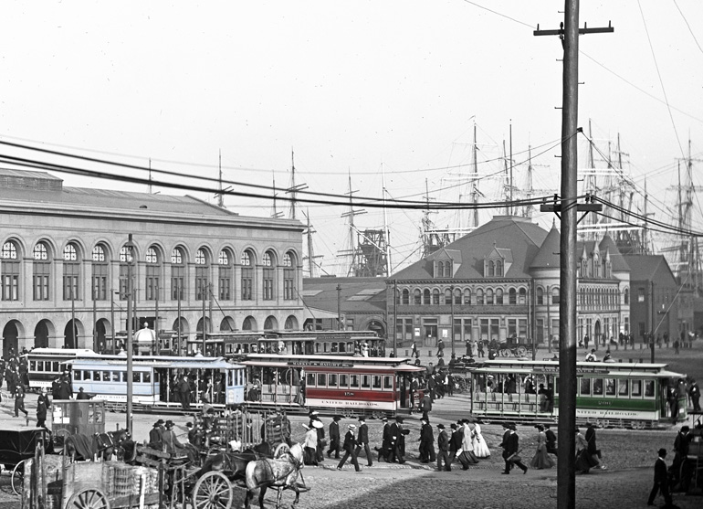 An image from the SFMTA Photo Archive looking towards the foot of the Ferry Building on Market Street in 1905.  There is a long line of cable cars, each with a different color of paint. The colors from left to right are light blue, bright red and dark green. The colors in this image have been added by hand and the background of the image is still in shades of grey. Tall ship masts can be seen in the San Francisco harbor in the background.