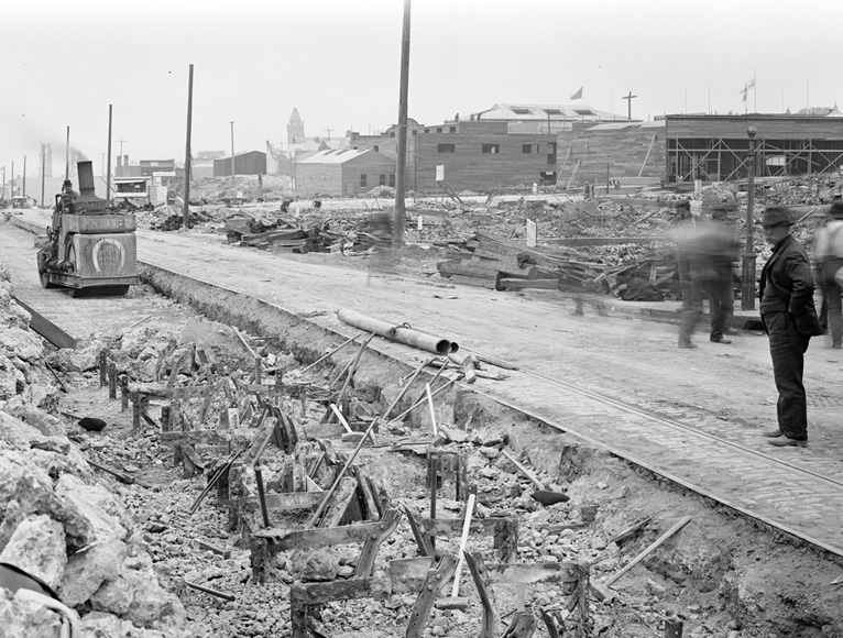 An image taken on July 20, 1906 shows a trench of metal structures from cable car tracks. Men appear to be at work to remove them, one of them driving a machine approaching the structures.