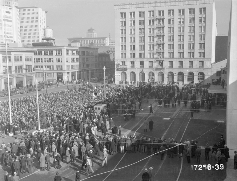 Overhead view of crowd of thousands of people gathered for the opening of the original Transbay Terminal on January 14, 1939 with downtown buildings in background.