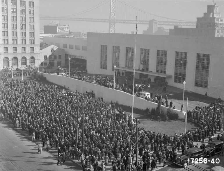 Overhead view of crowd of thousands of people gathered for the opening of the original Transbay Terminal on January 14, 1939 with San FRancisco-Oakland Bay Bridge and downtown buildings in background.
