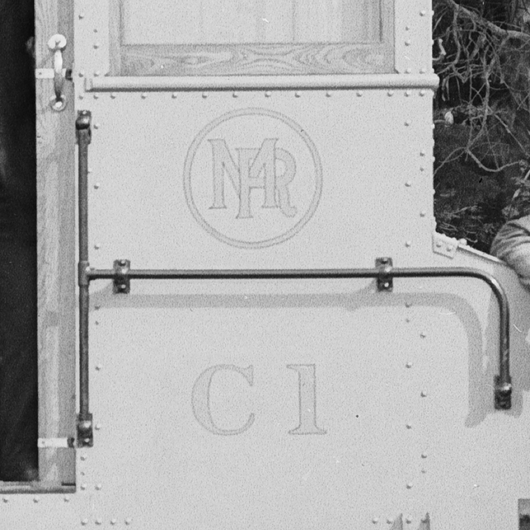Crop view of Gold-leaf Municipal Railway logo showing an overlapping 'M' and 'R' inside a circle.  Taken March 17, 1916