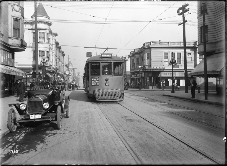 Black and white photo of a streetcar on the F Stockton line on Stockton Street, looking north from  just south of Vallejo Street, in late 1916. In the right foreground is a parked car, an early style Ford Model T. The street has pedestrians walking on both sides and street lamps with three large glass globes.