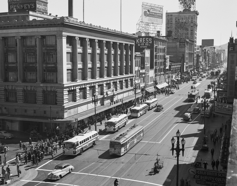 Black and white photo showing a view from above looking west/south west on Market Street from Eddy Street showing buses, streetcars, and pedestrians traveling on the street. Taken in July 1947.
