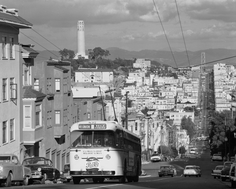 Black and white photo taken October 4, 1957 showing an electric trolley bus climbing Russian hill on Union Street. In the background is the North Beach Neighborhood and Coit Tower.
