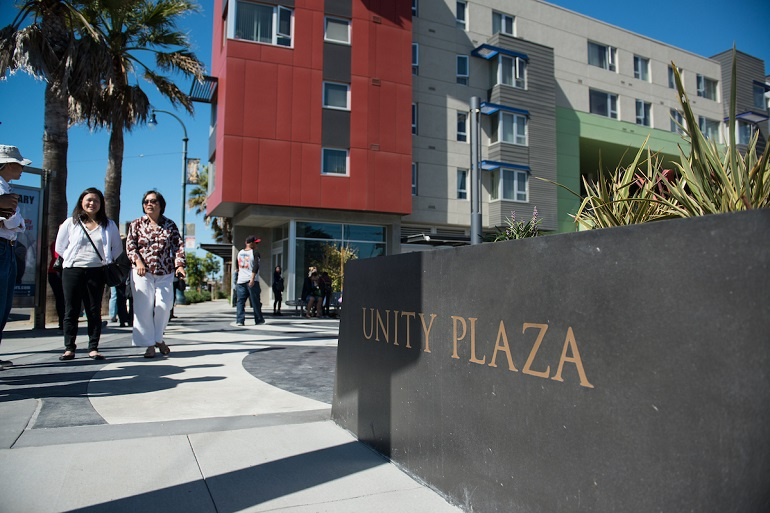 """Unity Plaza"" etched on a low wall along the sidwalk in front of an open plaza with pedestrians strolling past."