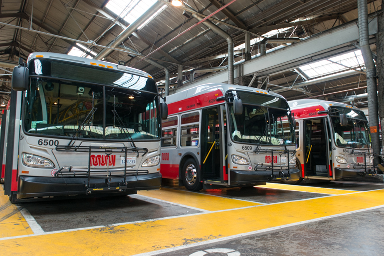 color photo taken in 2016 inside a Muni bus garage showing the fronts of three buses lined up in a row.  These buses are grey with red stripes along the top and bottom of the bodies.
