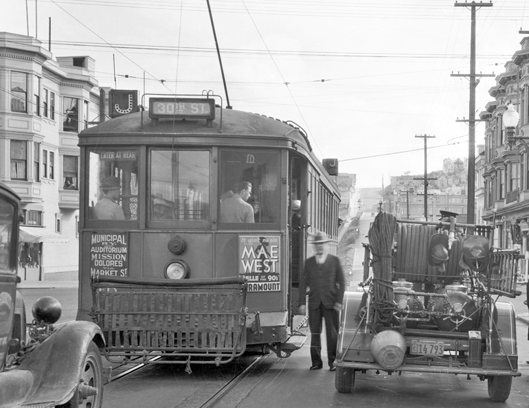 "black and white poto taken in 1934 on Church and 17th Streets.  A streetcar o the J line is stopped next to a fire truck and a man is standing between the fire truck and streetcar facing the camera.  The streetcar has a movie poster advertisement on the back reading ""mae west"""