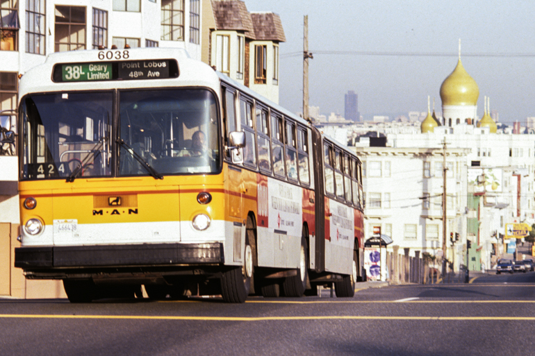"color photo taken in the 1980s looking east from Geary and 31st showing a long Muni bus painted in the ""sunset livery"", white with an orange and yellow stripe around the center of the bus.  In the background the golden onion shaped domes of a church rise above the cityscape."