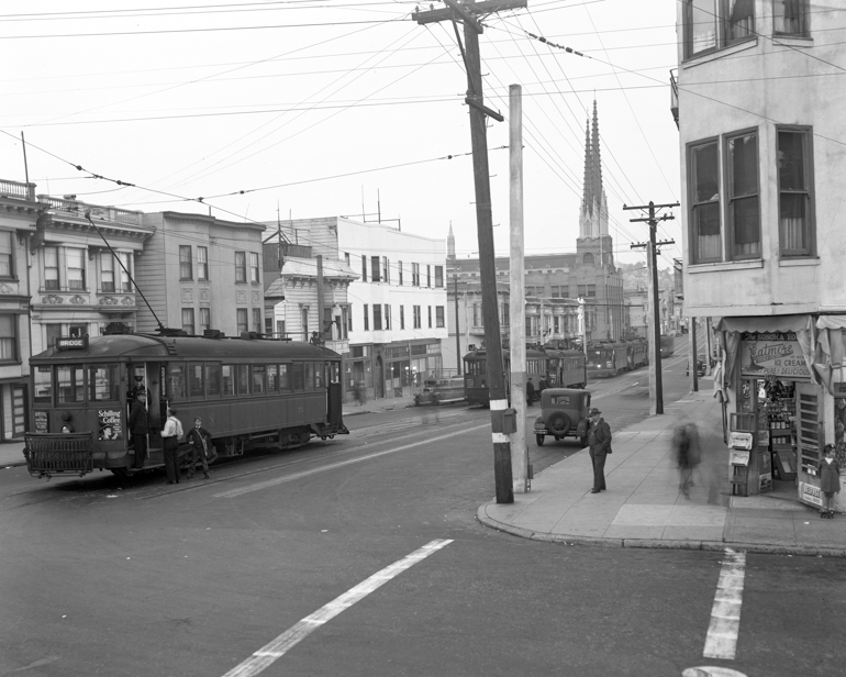 black and white photo showing multiple streetcars waiting at end of J line on 30th and Church streets on March 13, 1940.  The photograph was taken in the evening and several people moving about the street are seen as blurs.
