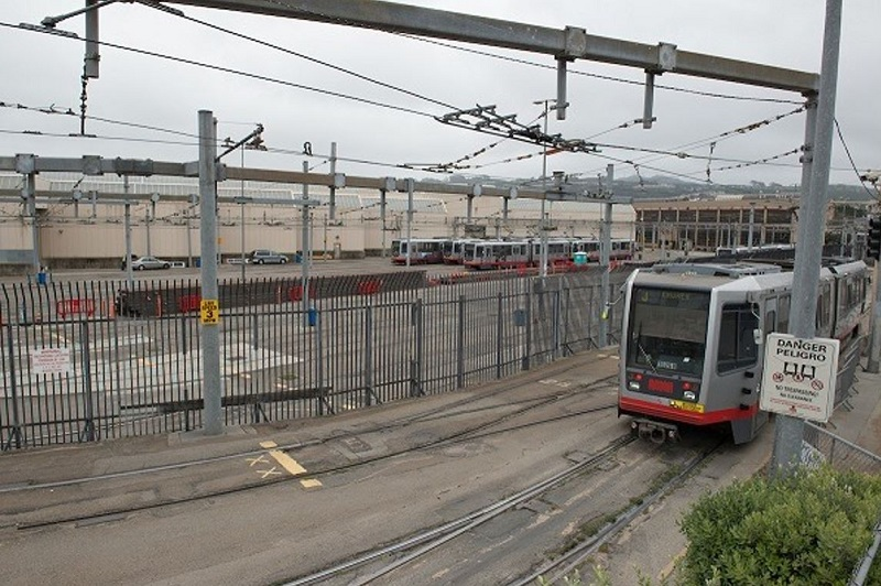 A light rail vehicles travels through the Green rail yard.