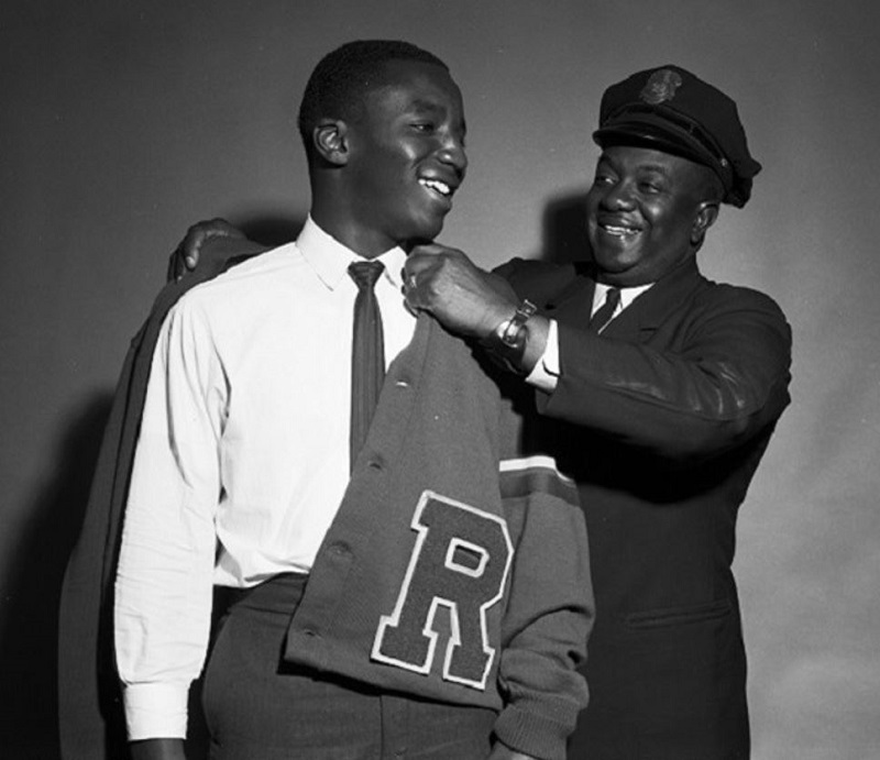 Black and white photo of a man in a Muni inspector cap putting a letter jacket on a younger man.