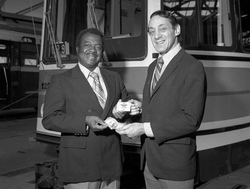 Black and white photo of Curtis Green and Harvey Milk standing in front of a streetcar.