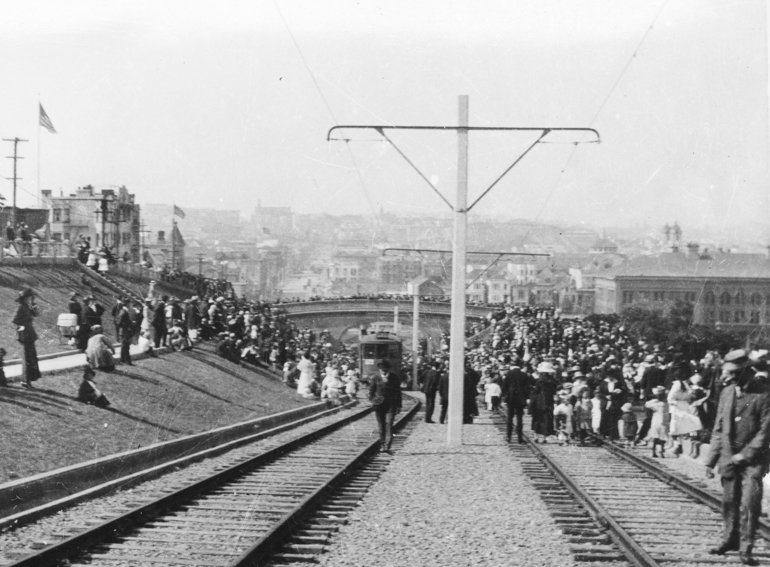 black and whit photo taken August 11, 1917 showing the opening ceremonies of the J Line.  A crowd of people swarms the tracks and pedestrian bridge in Dolores Park as streetcars make their way up the hill.