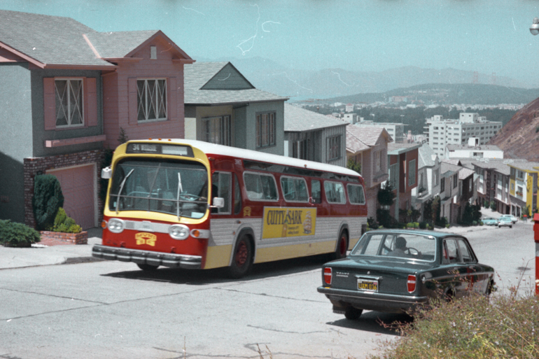 color photo showing a red, yellow, and silver painted Muni GMC bus climbing a hill in the Twin Peaks neighborhood in 1969.  Agreen volvo sedan is a right and the golden gate bridge towers can be seen faintly in the background.