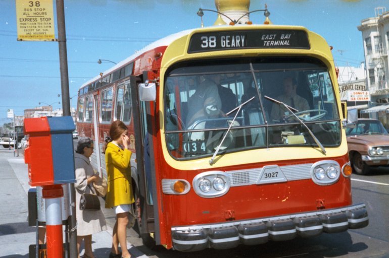 color photo taken in 1969 showing a red, yellow, and silver painted muni bus stopped at a stop on Geary Boulevard.  Two people, including a young woman wearing a mustard-yellow overcoat wait to board the bus.