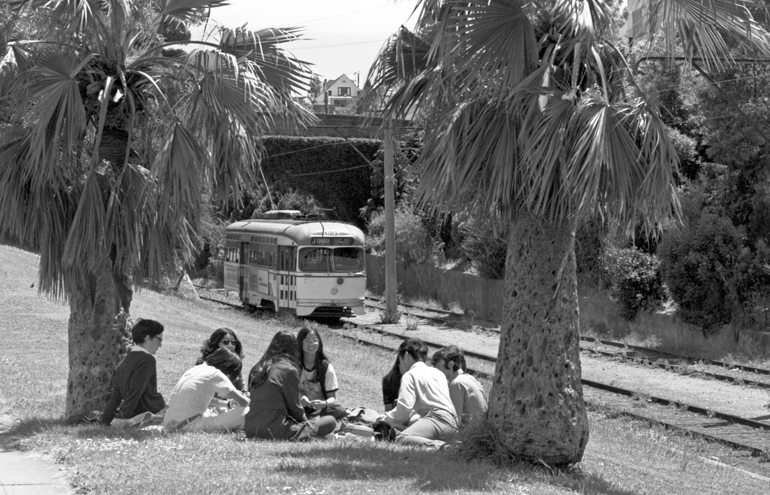 black and white photo from 1972 showing a group of youths sitting in a circle in a park, surrounded by palm trees with a streetcar passing by them in the background