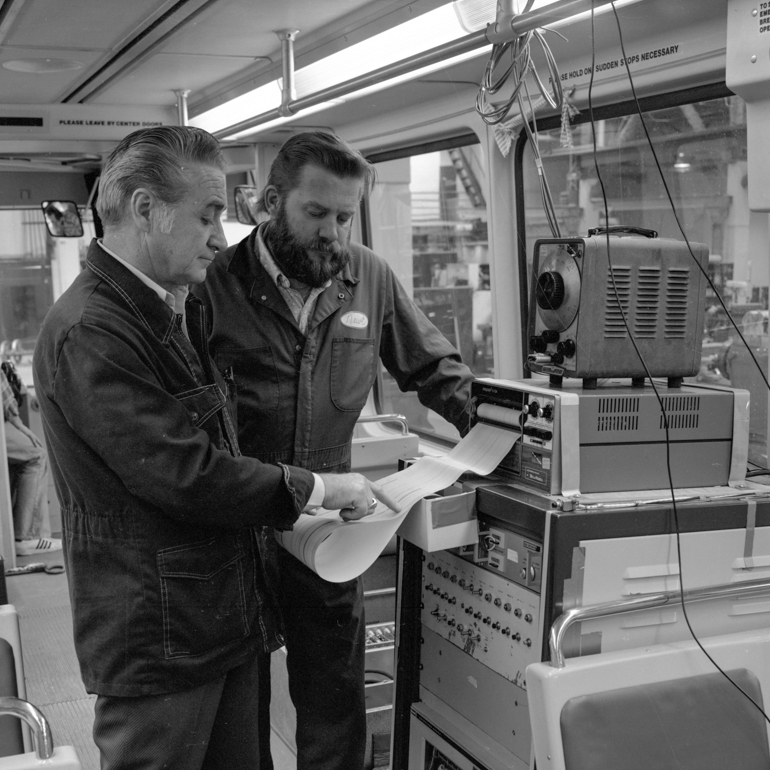 black and white photo showing two men standing in front of large computer inside Boeing Light Rail car looking at graph paper printout coming from machine.