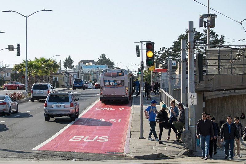 Pedestrians wait to cross in front of Balboa Park Station while a bus pulls up in the red transit-only lane and traffic passes on the left.