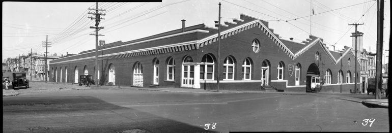 Black and white photo showing large brick building on Oak and Broderick Streets.  Building was used as a storage and repair facility for the Market Street Railway Company, taken October 1928