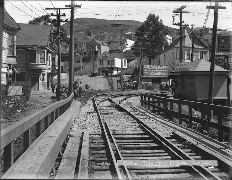 Black and white photo showing a view north on Diamond Street near Chenery in San Francisco's Glen Park Neighborhood. in the foreground is a wooden bridge and streetcar rails, followed by a street curving uphill with a handful of early 20th century wooden houses and buildings.