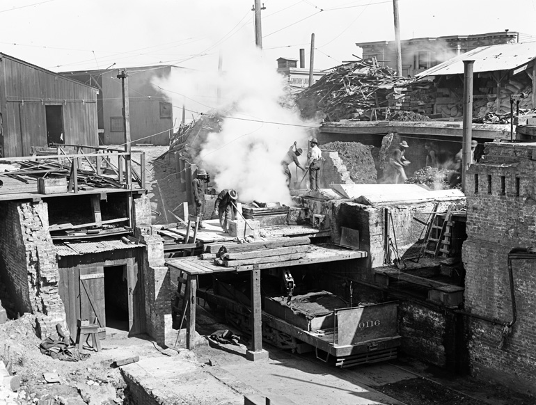 Black and white photo taken in 1910 of men working in an asphalt plant. A rail car sits in a brick-walled pit, above which men are moving steaming bins filled with hot asphalt.