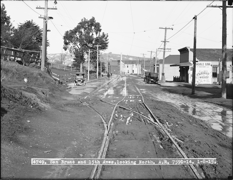 "Black and white photograph showing intersection of Bayshore Boulevard and Oakdale Avenue on January 8, 1915. Streetcar tracks receed into the distance away from the camera. to the left is a hillside covered with grass, trees, and some wooden fencing.  To the right is a small, flat-fronted building which houses the ""Oakdale Bar"", today this houses the Old Clamhouse restaurant."