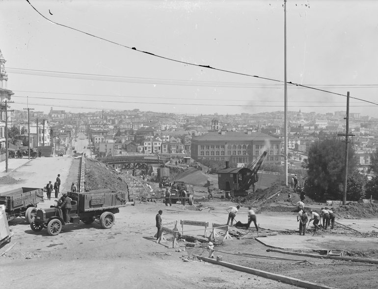 Black and White photo from 1916 showing a view south from 20th and Church Streets of J Line construction, Dolores Park, and the city skyline in the background.