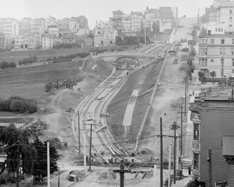 black and white photo taken in June 1916, looking south on church street from 17th at the construction of the J Line through Dolores Park.  The trackway is cut into the hillside in a serpentine fashion and workers are scattered about along the route digging and installing tracks.