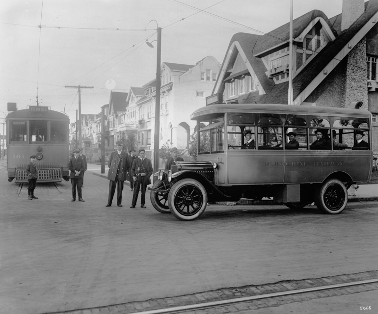 black and white photo taken in December 1917 showing a Muni streetcar with a bus from the first bus route at Fulton St and 10th Ave. People stand between the two vehicles facing the camera.