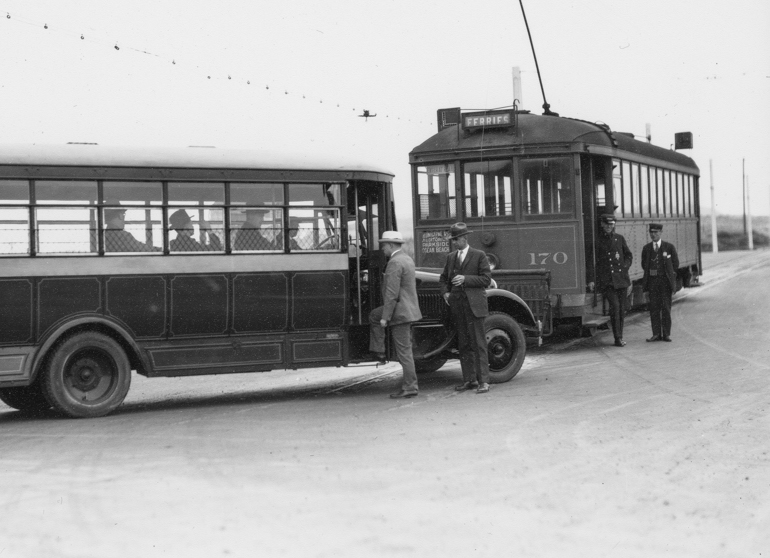 black and white photo showing people boarding a Muni bus in 1925 at the end of the L Taraval Line.  An L Taraval streetcar is seen in the background, amidst a wide open area of sand dunes in the undeveloped Sunset District.