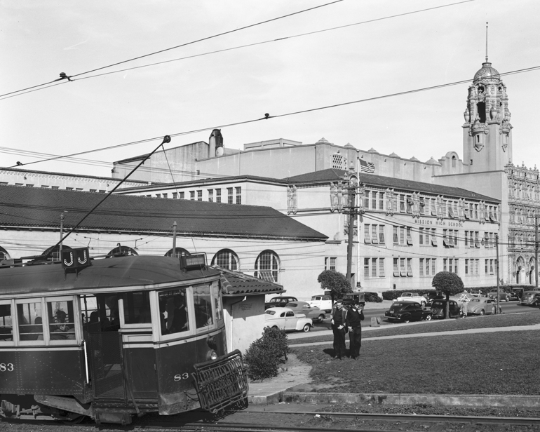 black and white photo showing a streetcar passing Mission High school in dolores park.  Two teenaged boys are standing to the right of the streetcar in the grass.