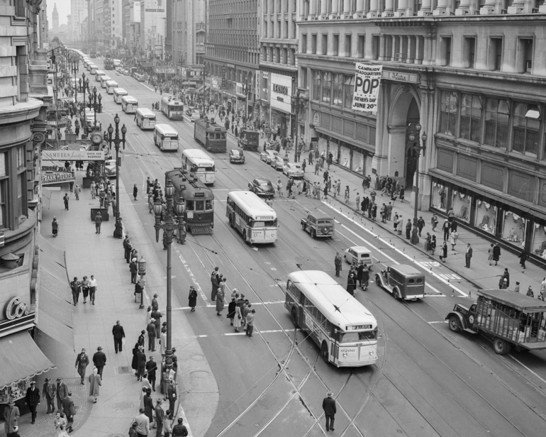 A black and white photo taken in 1948 looking east on Market Street from Powell, showing a long line of white colored motor buses parading down the street.  Taken from overhead, people stand on sidewalks watching the buses.