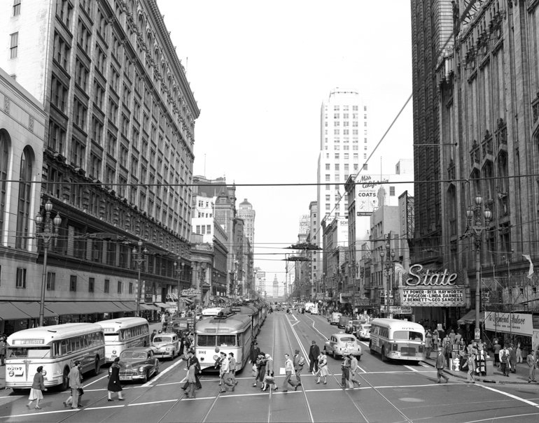 Black and white photograph showing an overhead view of Market Street, looking east from 4th Street.  Pedestrians are walking across Market at the bottom of the frame, with streetcars, buses, and automobiles mid-frame beyond. building facades flank the street at frame left and right.  Photo taken October 1, 1948.