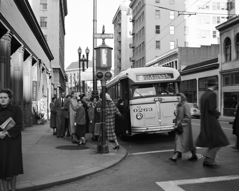 Black and white photo showing a group of people waiting to board a Muni bus in 1951.