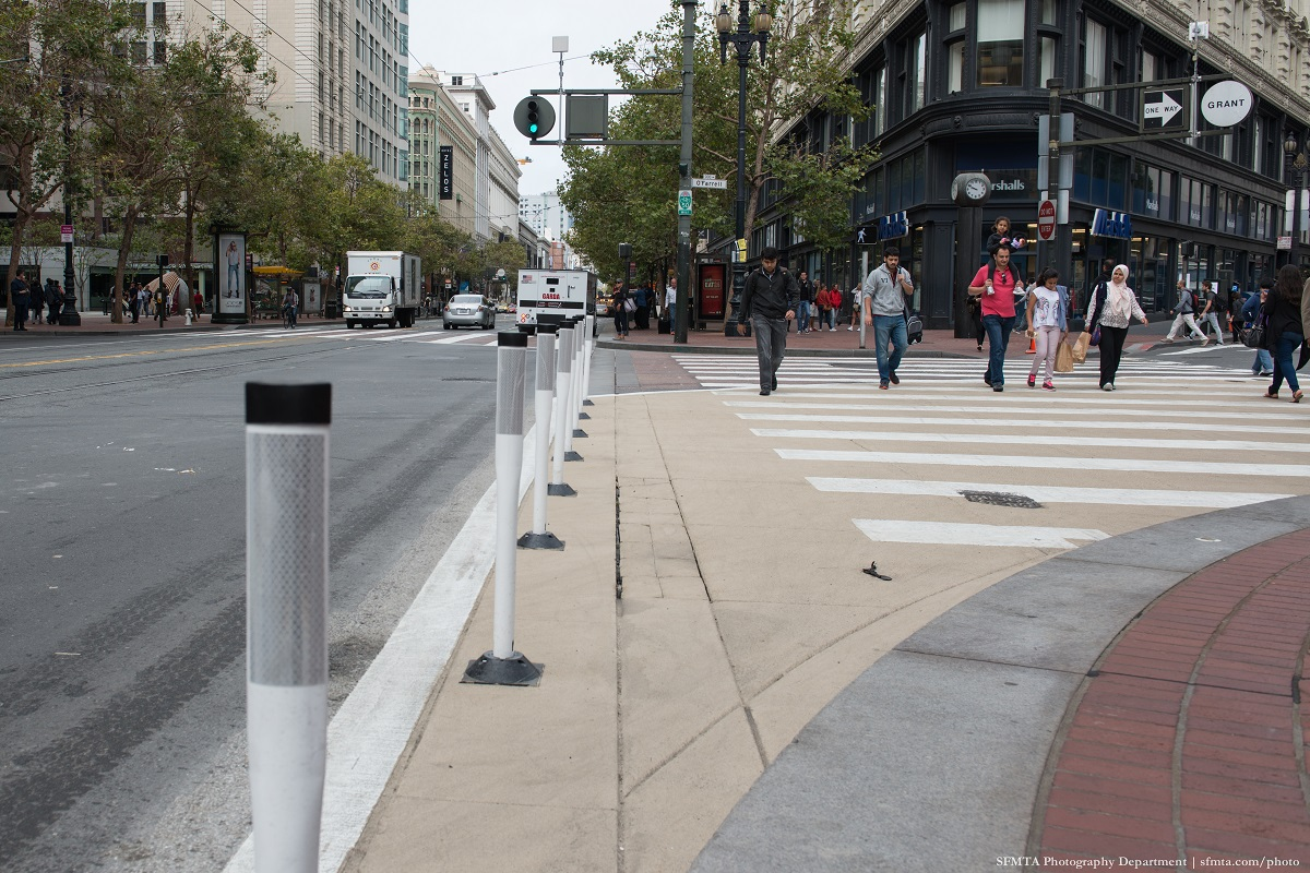 Safe-hit posts and zebra-striped continental crosswalks on Market Street.