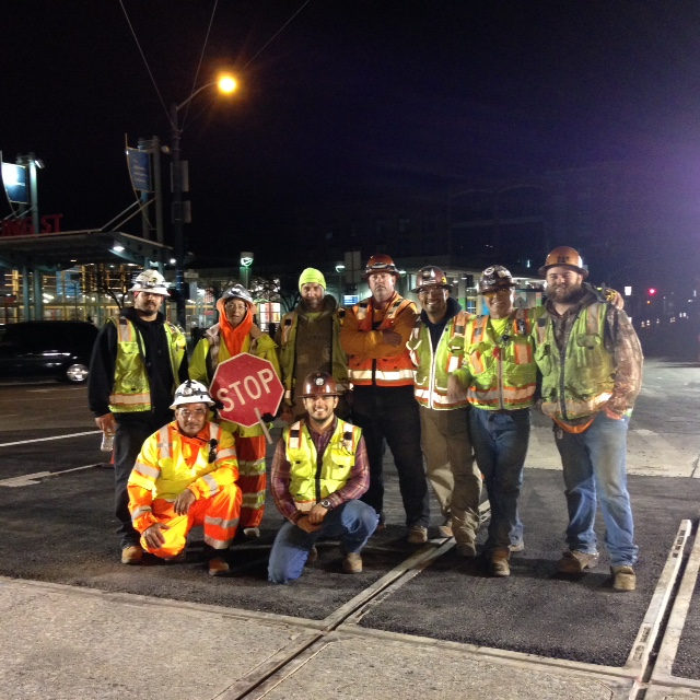 Group of construction workers stand and kneel at night with safety vests and hard hats with the Caltrain station behind them.