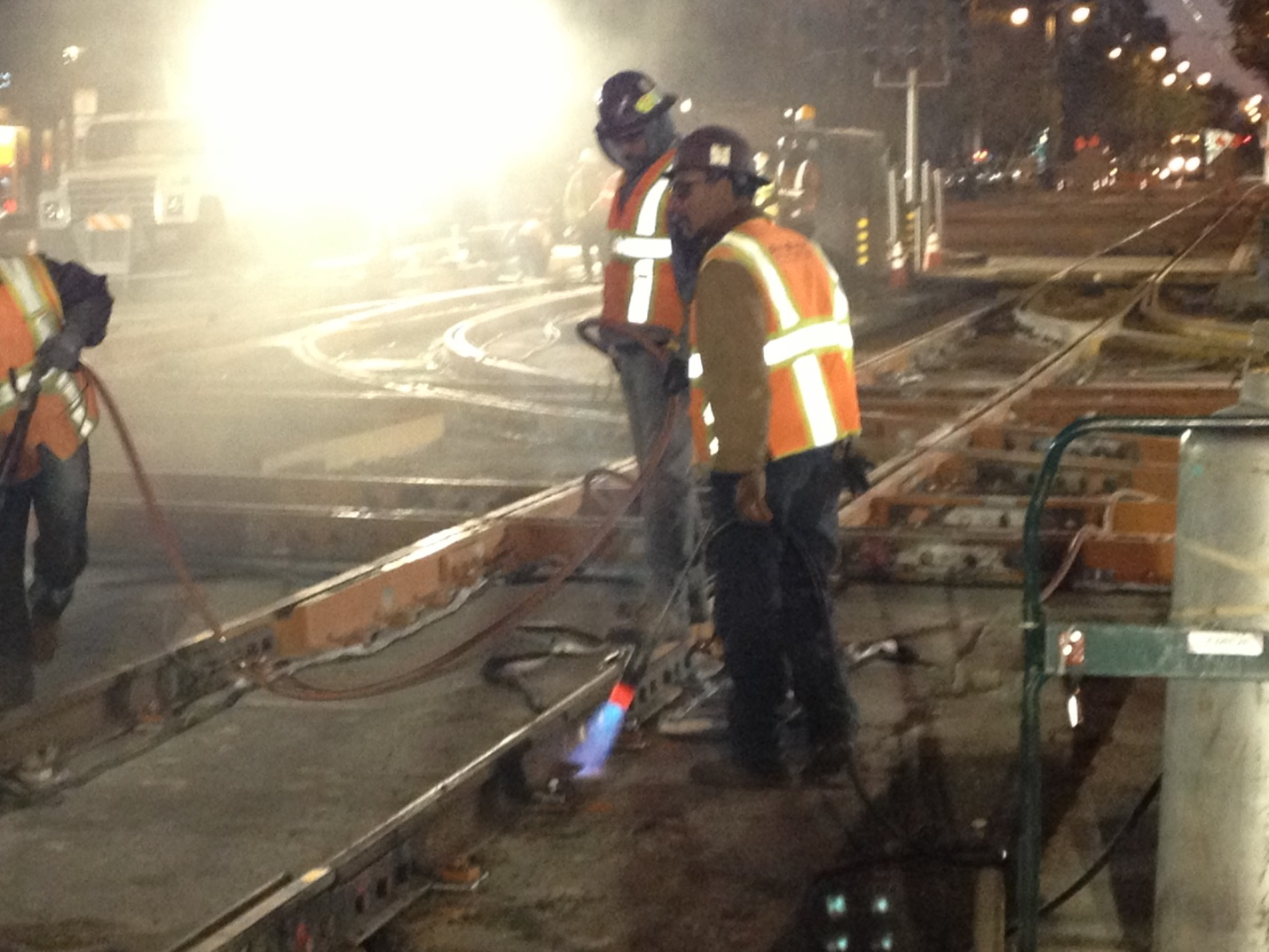 Crew members in safety vest and hard hats stand next to tracks being installed at 4th and King at night. Welding gear and safety strips are glowing
